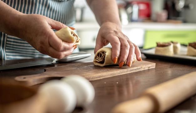 Mulher na cozinha cortando delicadamente a massa crua para fazer deliciosos pãezinhos de canela caseiros