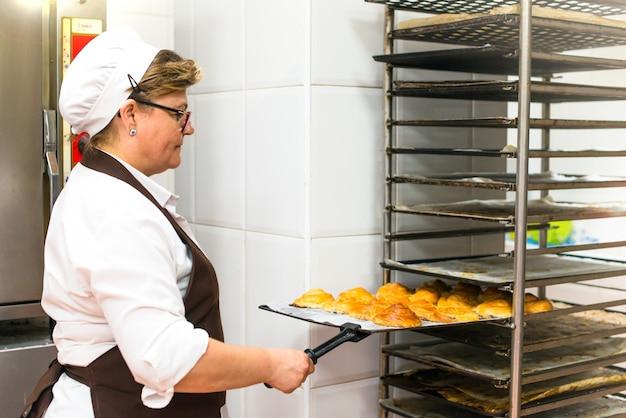 Mulher na cozinha de uma padaria cozinhar bolos