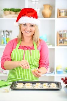Mulher na cozinha durante o preparo de biscoitos de natal
