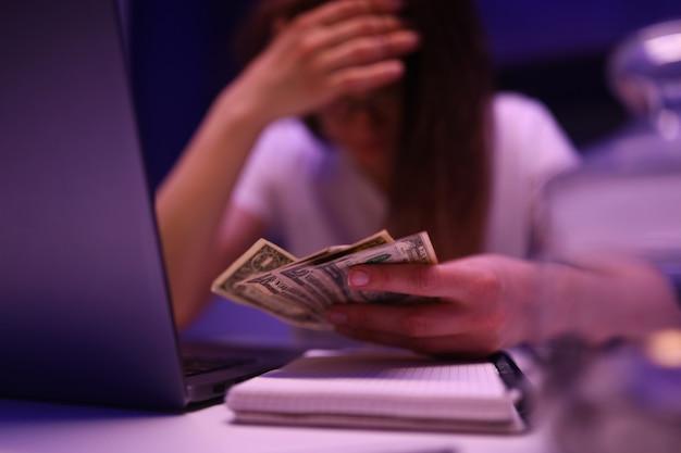 Mulher na cozinha é triste e conta o dinheiro que terminou na hora errada closeup fundo