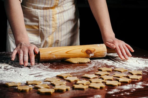 Mulher na cozinha está rolando massa na mesa de madeira com rolo de madeira
