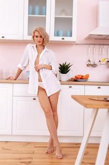 Mulher na cozinha. jovem loira descalça e magra com corte bob em pé na cozinha