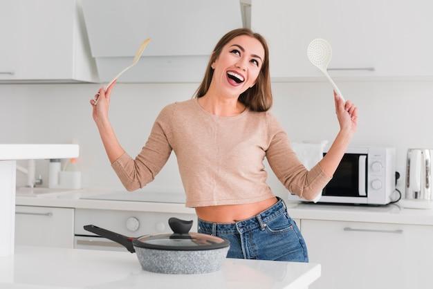 Mulher na cozinha segurando conchas