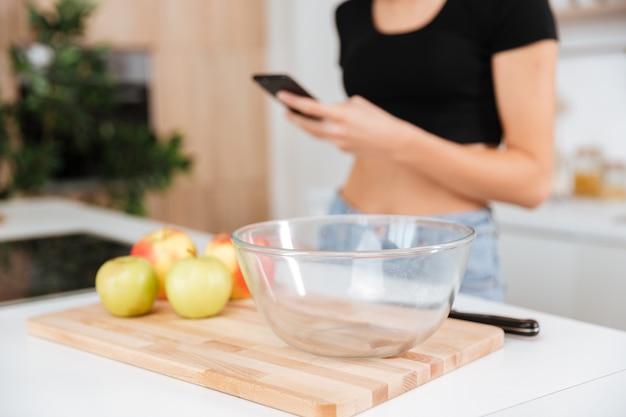 Mulher na cozinha usando o telefone