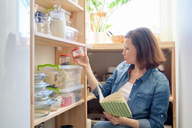 Mulher na despensa com mantimentos, prateleira de madeira para armazenamento de alimentos na cozinha, mulher com livro de receitas leva ingredientes