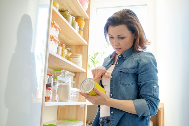 Mulher na despensa com mantimentos, prateleira de madeira para armazenar alimentos na cozinha.