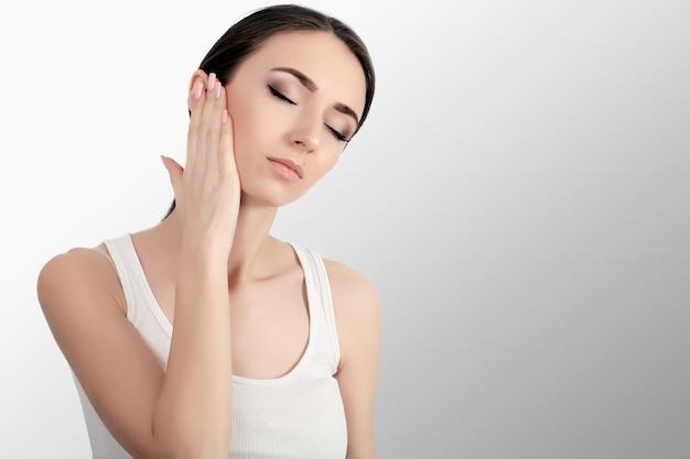 Mulher na dor. closeup de fêmea jovem bonita sentindo dor de dente dolorosa, tocando o rosto com a mão. menina estressada triste, sentindo os dentes fortes, mandíbula ou dor de garganta. cuidados e saúde bucal.