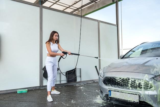 Mulher na estação de lavagem de carros self-service lavando a espuma do carro com mangueira de alta pressão