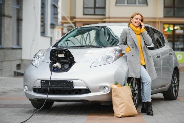 Mulher na estação de recarga de carros elétricos durante o dia