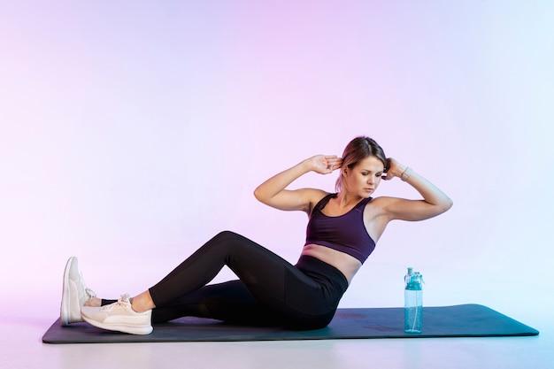 Mulher na esteira fazendo exercício abdominal
