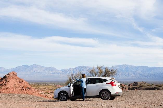 Mulher na estrada apreciando a paisagem