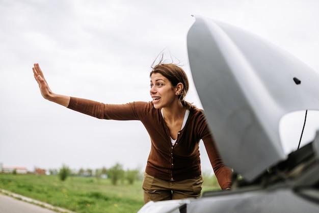 Mulher na estrada com o carro quebrado pedindo ajuda.
