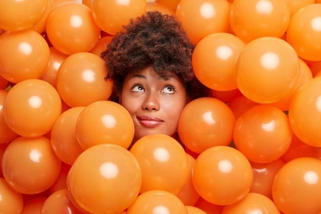 Mulher na festa de aniversário cercada por pequenos balões laranja