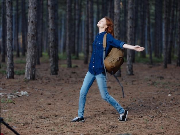 Mulher na floresta com uma mochila em uma caminhada de lazer ativo