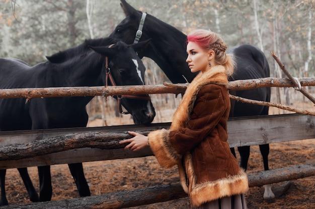 Mulher na floresta de outono com cavalos