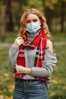 Mulher na floresta de outono. pessoa com máscara. tema coronavirus. senhora em um lenço vermelho.