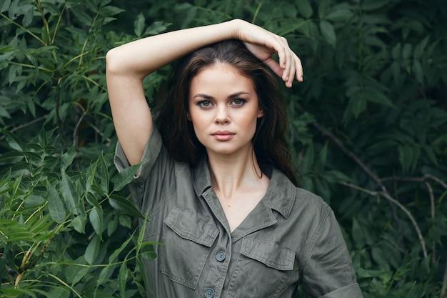 Mulher na floresta mantém a mão na cabeça e folhas verdes de macacão