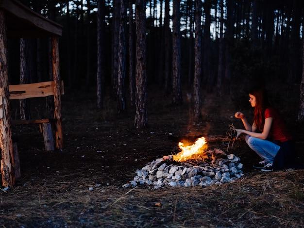 Mulher na floresta perto da fogueira, descanso na natureza, noite