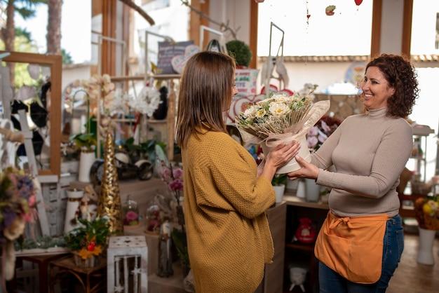 Mulher na floricultura com uma caixa branca de flores, vendedora