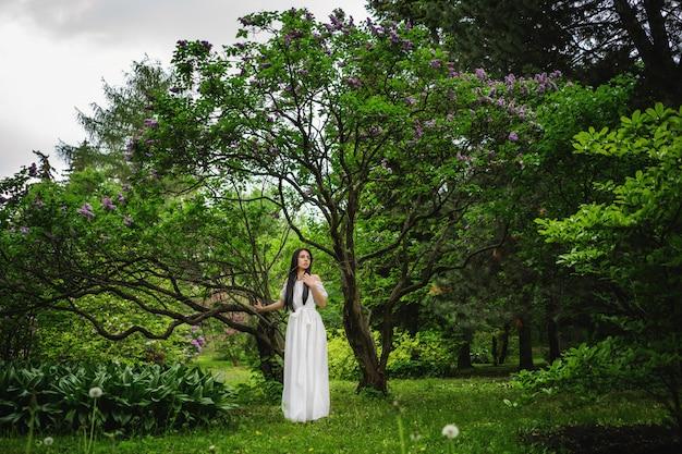 Mulher na frente da grande árvore no parque.