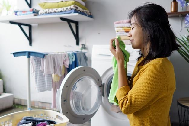 Mulher na frente da máquina de lavar lavando roupa carregando roupas dentro