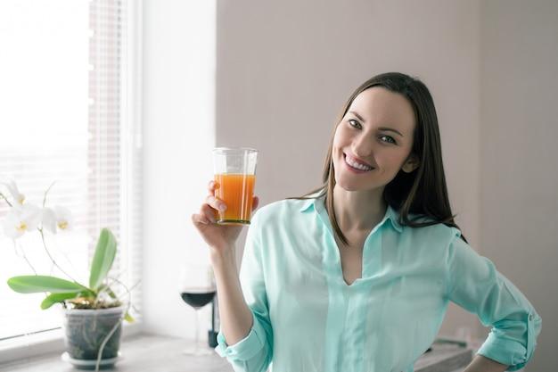 Mulher na janela da cozinha, sorrindo e segurando um copo de suco