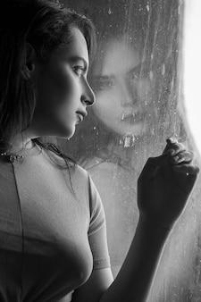Mulher na janela, olhando para a chuva, preto e branco