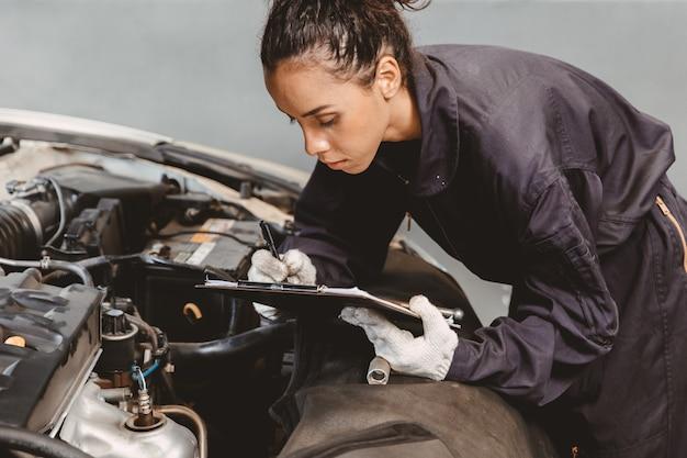 Mulher na lista de verificação de manutenção do trabalhador de garagem no centro de serviço automotivo, mulher no mecânico de automóveis, técnico de automóveis, verificar e consertar o carro do cliente, inspecionando o carro sob o capô