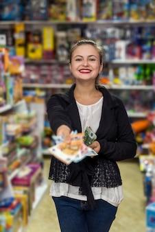 Mulher na loja de brinquedos oferecendo notas de euro