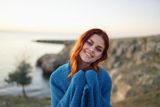 Mulher na manta azul da natureza admira a viagem da paisagem. foto de alta qualidade