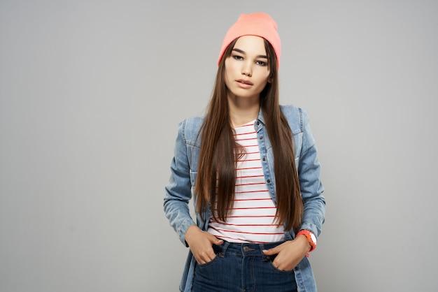 Mulher na mão de camisa jeans de chapéu-de-rosa perto do estúdio de rosto. foto de alta qualidade
