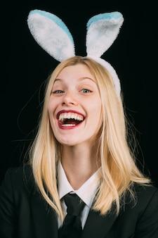 Mulher na máscara de coelhinho da páscoa da moda. mulher feliz em orelhas de coelho ri.