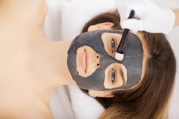 Mulher na máscara no rosto em salão de beleza de spa.