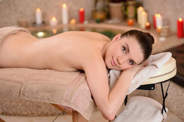 Mulher na massagem dos termas do corpo no salão de beleza.