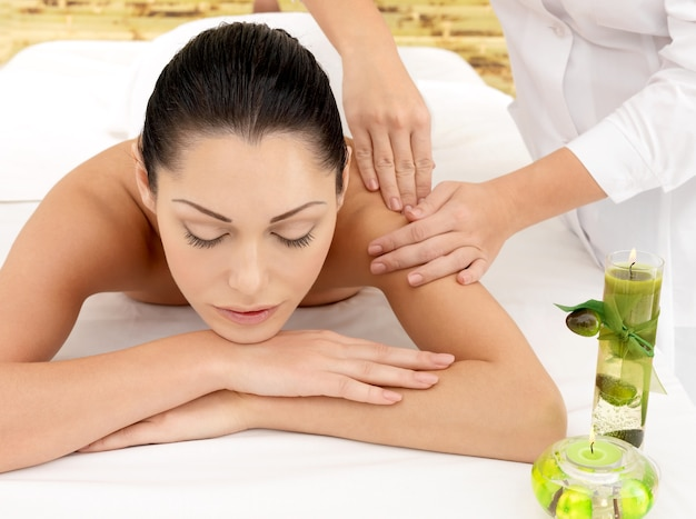 Mulher na massagem spa do ombro no salão de beleza.