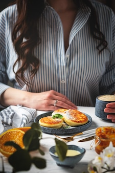 Mulher na mesa com um café da manhã bonito e saboroso. panquecas de requeijão em um prato, copo com café e laranjas em um fundo branco de madeira.