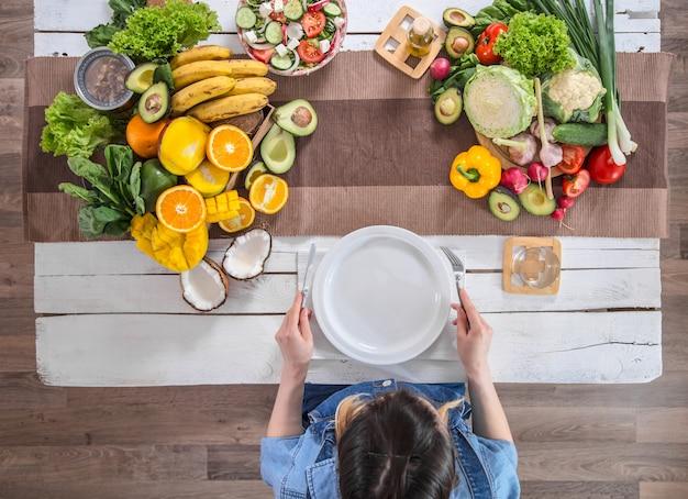 Mulher na mesa de jantar com alimentos orgânicos