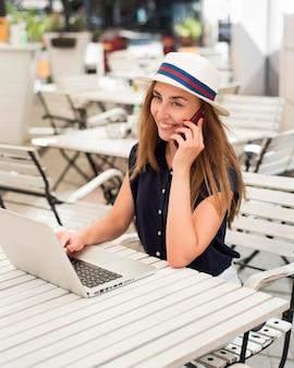 Mulher na mesa falando ao telefone e usando laptop