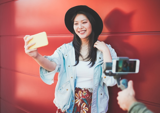 Mulher na moda asiática vlogging enquanto estiver usando o smartphone ao ar livre. feliz menina chinesa se divertindo com as novas tendências da tecnologia