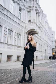 Mulher na moda blondie jovem bonita posando de casaco na moda na moda ao ar livre. beleza, moda, conceito de modelagem