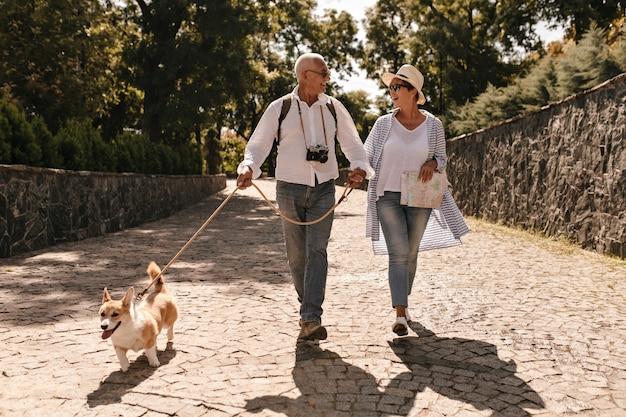 Mulher na moda com chapéu e blusa azul andando e olhando o homem de cabelos grisalhos na camisa de manga longa branca com câmera e corgi no parque.