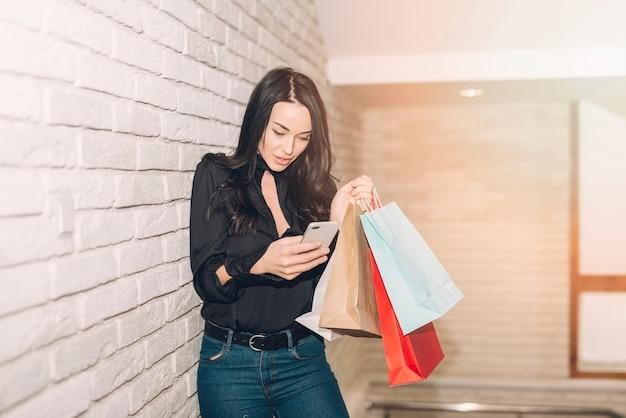 Mulher na moda com sacos usando o telefone