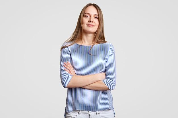 Mulher na moda confiante, com longos cabelos lisos, mantém as mãos cruzadas, ouve informações do interlocutor