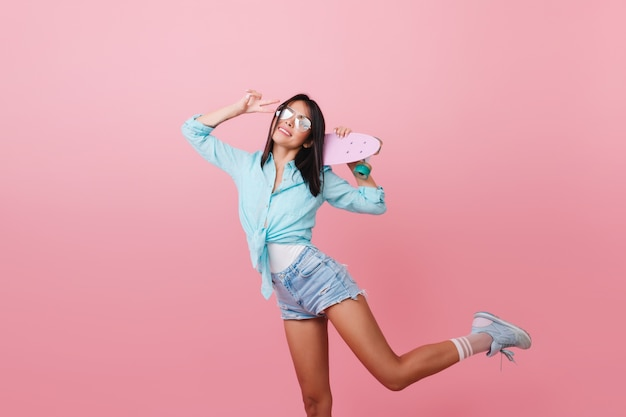 Mulher na moda de cabelos negros com bronzeado dançando com longboard rosa e rindo. desportiva menina asiática de camisa azul e óculos escuros em pé em uma perna com o símbolo da paz.