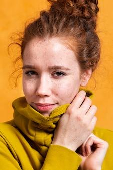 Mulher na moda de close-up posando com capuz amarelo