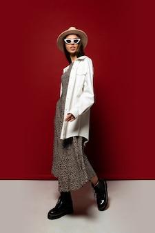 Mulher na moda elegante em jaqueta branca e vestido posando. botins em couro preto. comprimento total.