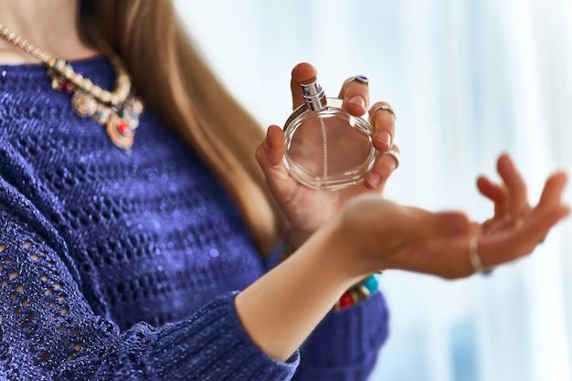 Mulher na moda elegante, usando jóias, aplicar perfume no pulso