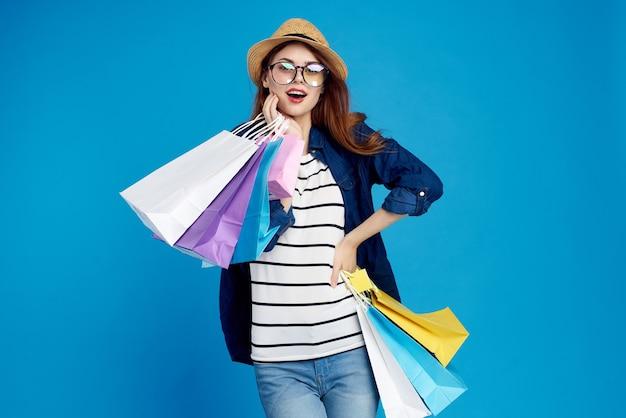 Mulher na moda está comprando pacotes em um fundo azul em uma camiseta