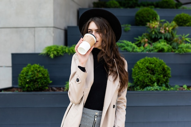 Mulher na moda jovem feliz bebendo café e andando depois de fazer compras em uma cidade urbana.