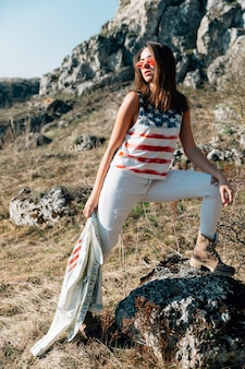 Mulher na moda legal permanente na pedra na luz solar